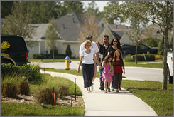 Jim and Maryanne Cerra go for a walk with their granddaughters, Jillian, 5, Julia, 7, and Jeana, 2, while son-in-law Jim Dunden and daughter Jen Dunden follow behind in DeLand, Fla. The family lives in the first wave of what could become a future staple of U.S. housing  the multigenerational community.