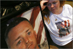 Mary Gallagher looks at a photo of her husband Gunnery Sgt. James F. Gallagher at her home in Lynbrook, N.Y. Mary's husband committed suicide at Camp Pendleton in May 2006. The image on Mary's shirt is also of her husband.