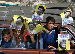 Children of displaced families returning to southern Lebanon show pictures of Hezbollah leader Sheik Hassan Nasrallah near Zahrani on Aug. 14, 2006. Hezbollah dropped leaflets, held rallies and distributed food. The U.S. has learned that in such a conflict, soldiers skilled in communication need to be on the front line not for propaganda, but to explain U.S. actions.