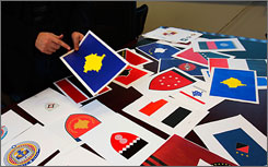 Fadil Hysaj, a Kosovo Albanian artist and political adviser, looks over designs submitted for an independent Kosovo's flag in his office in Pristina, Serbia, Wednesday.