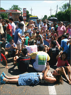 A crowd of people block a main highway on the outskirts of Asuncion, Paraguay, in protest to demand yellow fever vaccinations on Wednesday.