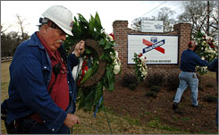 Employees of the Imperial Sugar plant carry eight wreaths to a sign at the front gate of the plant, after a fire at the plant claimed eight lives in Port Wentworth, Ga.