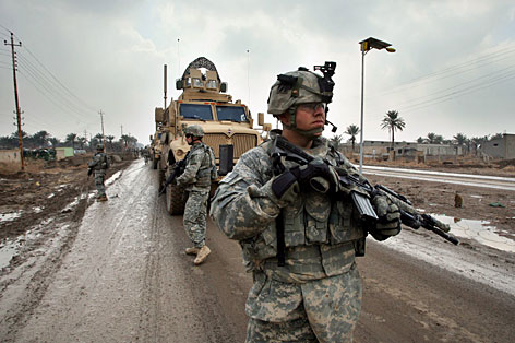 Soldiers from the 3rd Infantry Division scan an area for roadside bombs near Baghdad last month.