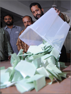 Electoral officials empty a ballot box at the end of the polling in Karachi on Monday. Vote counting began after polls closed at 5 p.m. Pakistan time, and full results aren't expected until Tuesday.