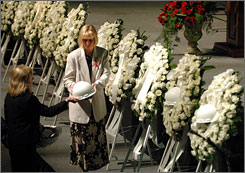 Imperial Sugar employee Ginger Faulconer, center, places hard hats on 10 wreaths during a memorial service, in Savannah, Ga., for the victims of a explosion at the plant earlier this month.
