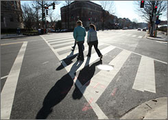 Pedestrians use a crosswalk on Connecticut Avenue in Washington. The city plans to add crossing signals developed in Arizona in about 30 places.
