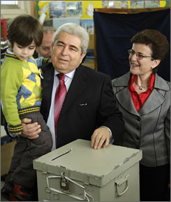 Presidential candidate Dimitris Christofias, center, escorted by grandson Demetris, left, and wife Elsi, casts his ballot.