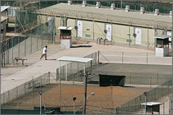 A Guantanamo detainee, center left in white, jogs around the exercise area at the medium security portion of the Camp Delta detention facility, at the Guantanamo Bay U.S. Naval Base, Cuba, in September 2006.