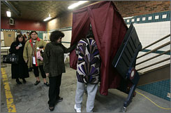Poll workers Modestine Chung, on the right with her head in voting machine, and Aida Nieves, second from right, look at a voting machine that was not working as voters waited at a polling place at a fire house in Hoboken, N.J. on Feb. 5.
