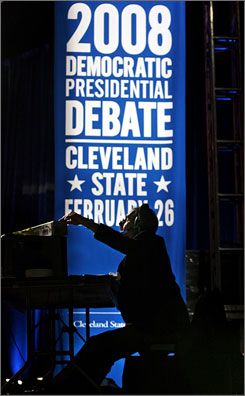 A crewmember watches on a monitor on Monday as the stage is fine tuned for Tuesday's Democratic debate in Cleveland.