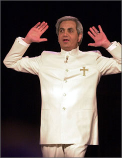 Evangelist Benny Hinn raises his hands in prayer during a service at the Blaisdell Concert Hall in Honolulu in January 2002. Hinn has turned over financial records to the Senate Finance Committee in response to a request from Sen. Charles Grassley, R-Iowa.