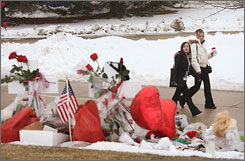 Students Tina Zambuto. left, and Christina Billich pass by a memorial to slain students on the campus of Northern Illinois University on Monday in DeKalb, Ill.