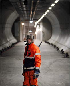 An armed guard stands in the entrance tunnel to the Svalbard Global Seed Vault. This long, steel-lined tunnel leads to three separate chambers for storing seeds, each reached through a frost-covered metal door. Each of the 32-by-88-foot vaults has blue and orange metal shelves that can hold 1.5 million sample packages  foil containers with 500 seeds each.
