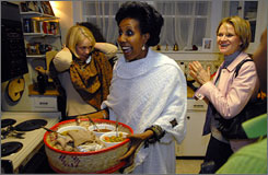 Marsha Wallace, left, Atu Bekele, center, and Cathy Grant, right, attend a Dining for Women meeting at the home of Jo Prostko in Greenville, S.C., on Feb. 18, 2008.
