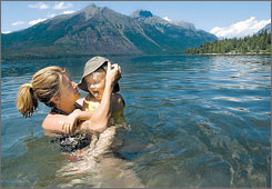Elan West-Badminton, 4, right, of Monteverde, Costa Rica, enjoys the waters of Lake McDonald with her mother, Kim West, in this 2004 file photo, taken in Glacier National Park in northwest Montana.