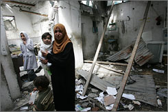 Palestinian women stand in rubble in a home in Gaza City. The baby's father was killed during an Israeli aircraft strike near the home of Hamas' Interior Minister.