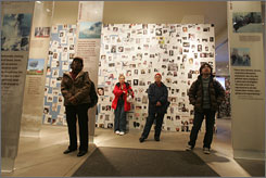 Visitors to The Tribute Center watch a video in front of a wall of posters of the missing near the World Trade Center Ground Zero area on Feb. 27.