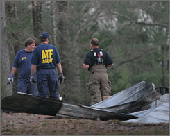 Federal investigators from Rains and Smith counties, Texas shovel and pick through charred remains of a rural Alba, Texas, home on Saturday evening.