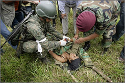 Ecuadorean military personnel administer first aid to Colombian FARC rebel Martha Perez, who was injured when Colombian troops crossed into Ecuador to attack the leftist camp.