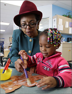 Dayton Mayor Rhine McLin helps pre-schooler Ettinne Golladay, 3, create a cinnamon bear at United Rehabilitation Services of Greater Dayton. Her signature hats help cover bad hair days guaranteed with her hectic schedule, she jokes.