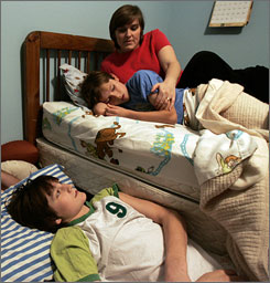 Lynne Bruton helps sons Clint, left, and Dale wind down before bed at home in Abilene, Texas. Bruton has found that giving 14-year-old Clint and 10-year-old Dale melatonin helps them sleep better and wake up fresh.