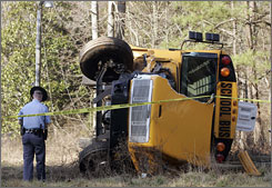 A Georgia State trooper looks over the wreckage of an overturned school bus crash in Canton, Ga., March 3.
