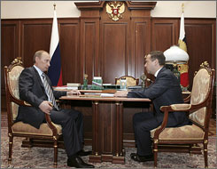 Russian President Vladimir Putin, left, speaks with First Vice Premier Dmitry Medvedev during their meeting in the Kremlin in Moscow on Monday. Europe's press poured scorn today on Russia's carefully choreographed presidential election.