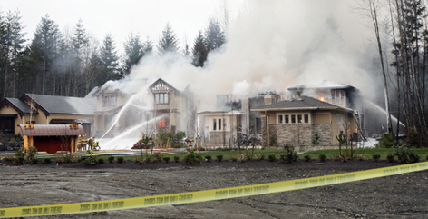 Firefighters try to douse an unoccupied luxury home in Woodinville, Wash., a Seattle suburb, where three of five model homes were razed.