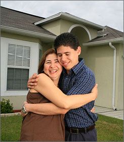 "Nancy Cadavid, 44, hugs her son Eduardo, 20, outside their home in Kissimmee, Fla. Colombian by birth, Cadavid works two jobs and is a homeowner. ""I love this place,"" she said."
