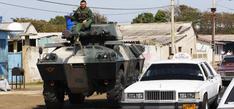 A Venezuelan soldier rides atop an armored personnel carrier as it drives through the town of Paraguaipoa towards the border with Colombia, Tuesday. Tensions escalated when Colombian troops killed a top commander of the Colombian FARC rebels, angering Venezuela's leftist President Hugo Chavez.