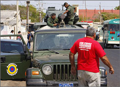 Venezuelan soldiers prepare an armored personnel carrier as it drives through the town of Paraguaipoa, Tuesday.