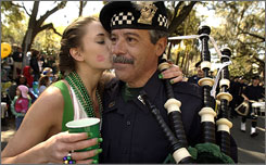 Christy Coberly kisses Long Island, N.Y., Police Pipe and Drum Band member George Lago on the cheek at last year's St. Patrick's Day parade in Savannah, Ga. For religious reasons, the city will hold the parade on March 14. Some say festivities promote drunkenness rather than honoring the saint.