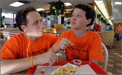 McKay Hatch, 14, the founder of a 10,000 member-strong No Cussing movement, jokes with his father, Brent Hatch, right, at his dad's restaurant, Wednesday.