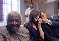 Sitting next to Archbishop Desmond Tutu, left, a cozy French President Nicolas Sarkozy and his wife Carla Bruni-Sarkozy appear giggly in their visit to Gugulethu AIDS Institute near Cape Town, South Africa.