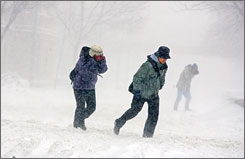 Pedestrians brave high winds and blowing snow as they make their way across the University of Wisconsin campus in Madison, Wis., on Feb. 6.
