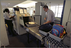A Transportation Security Administration screener checks carry-on luggage as a passenger loads his baggage at Newark (N.J.) Liberty International Airport in November.