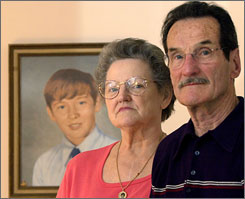 Carl and Bunny Croteau stand in front of a portrait of their murdered son, Danny, in their Springfield, Mass. home March 27, 2003.  The Croteaus have suspected a priest in the April 1972 murder of their son however, the Hampden district attorney's office released 115 pages of documents related to the unsolved case on Feb. 22 which provide no new clues about who may be responsible for Croteau's death.