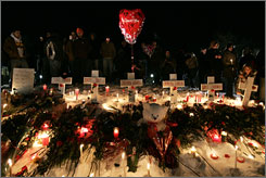 Students gather around a makeshift memorial Feb. 15 after a campus vigil on Northern Illinois University campus in DeKalb, Ill.