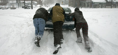 A motorist gets help after his car got stuck in the deep snow Saturday, in Columbus, Ohio. A foot of snow buried parts of the Ohio and Tennessee valleys early Saturday, shutting down travel and many public events. Blizzard warnings remain in effect.