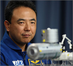 Satoshi Furukawa, astronaut with Japan Aerospace Space Agency, looks at a model of the Kibo experiment logistics module during a briefing Saturday at the Kennedy Space Center in Florida. The Japenese experiment logistics module will be carried into space with Endeavour on March 11.