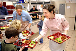 Chef Jenna Ortner hands out lunch with the help of a parent volunteer at Holy Cross Academy in Stafford, Va.