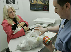 Julie Benesh meets with veterinary technician Daniel Scogin in Chicago in 2007 after the food she was feeding her cat Truffle was recalled. Tainted pet food is believed to have killed hundreds of pets in the outbreak.