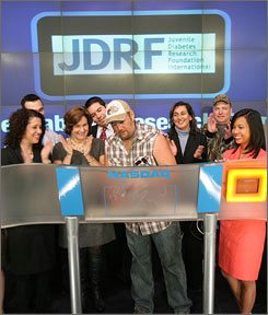 "Dan Whitney, better known as ""Larry the Cable Guy,"" center, showed off better-toned arms with his signature sleeveless plaid shirt as he joined the Juvenile Diabetes Research Foundation team for the opening bell at the NASDAQ MarketSite Feb. 21."