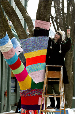 """Nancy Mellon adds another section of knitting to the """"Knit Knot Tree"""" on  Xenia Avenue in Yellow Springs, Ohio."""