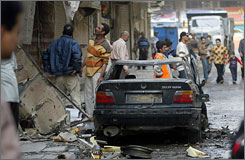 Iraqis inspect the site of a suicide attack in Baghdad's Bab al-Sharji area.
