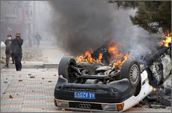 A burning car sits on a street in the Tibetan capital Lhasa after protests spread.