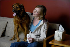 "Lynn Stockmaster and her dog Logan sit in her Rochester, N.Y., home. She says she's ""definitely less social"" when affected by pet dander and other allergens."