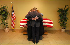 Pastor Rog Hosier, center, leads the Anzack family in prayer in front of the casket of Pfc. Joseph Anzack Jr. on May 29, 2007, in Torrance, Calif. Anzack was captured May 12, 2007, by enemy forces in Al Taqa, Iraq.