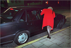 A woman identified as a prostitute talks to someone in a car in central Stockholm.