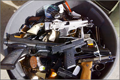 "A pile of guns are collected in a garbage can after volunteers turned-in about 500 firearms for money as part of the ""One Less Gun"" event  in Oakland,  Calif., on Feb. 9.  The response was so overwhelming that police issued $170,000 in IOUs."